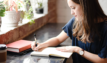 A woman jots down notes in a notebook.