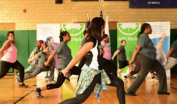 A whole class of people strikes a pose in a gym.