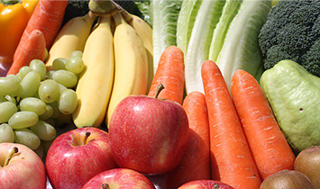 Close up of fruits and vegetables like apples, carrots, and grapes.